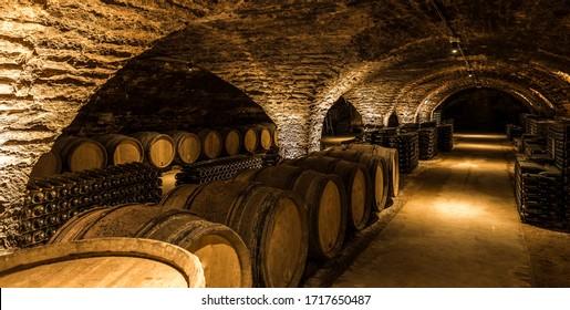 Old cellar with bottles and barrels under castle making wine