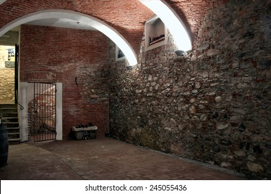 An old cellar in Piedmont Italy recently restored with red bricks arches and brick floor.Some wine bottles and a wooden cask. An iron gate in the background.