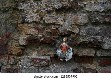 Old ceramic doll pasted into the brick wall. Horizontal shot