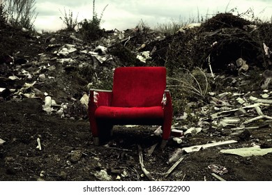 The old chair is in a landfill. Abandoned wasteland with waste and garbage.