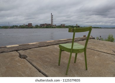Old chair on the background of an abandoned factory. Jetty on the river