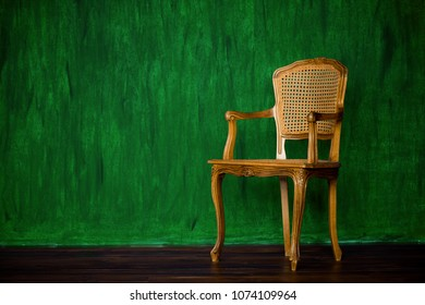 old chair on a green wall background.