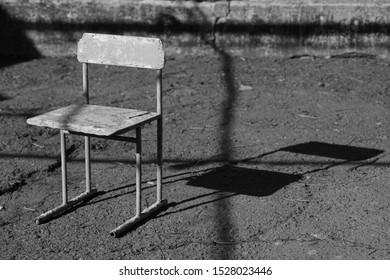 Old chair in the rural yard. Asphalt stone floor. Hard light and shadow. BW