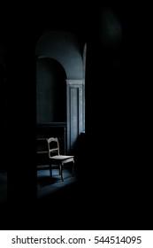 Old chair standing in a dark room near the window, on the old floor beside an empty locker.