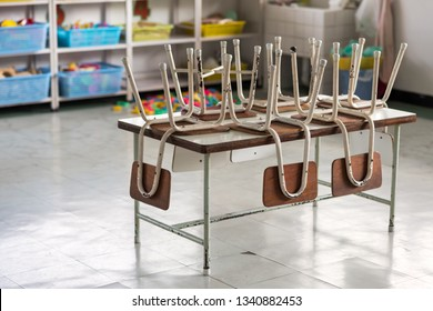 Old chairs on table with many blurred toys and study equipments of kindergarten room. empty classroom without any student. End of school semester concept.