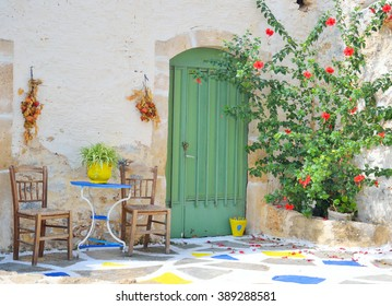 Old chairs and a small table next to the old house in Malia, Crete, Greece.