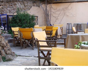 old chairs and tables in blue and yellow in an Restaurant Taverna Bar Café in Greece