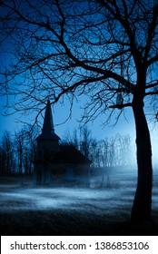 Old chapel on haunted creepy graveyard at night