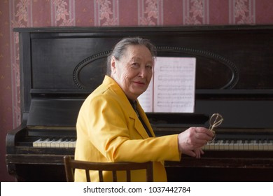 Old charming lady pianist in the yellow jacket seating at the piano