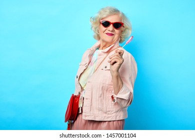 Old cheerful happy lady with sunglasses holding lollipop and looking at the camera on a blue background. sweets, love, valentine's day. fashion concept