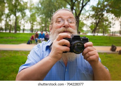 Old cheerful man with long beard making picture in green park