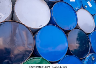 Old chemical barrels. Blue, white, and green oil drum. Steel oil tank. Toxic waste warehouse. Hazard chemical barrel. Industrial waste in old drum. Hazard waste storage in factory. Metal barrels.