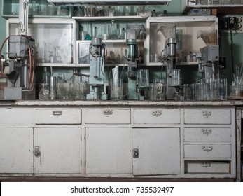 Old chemical laboratory with equipment and a table with glass flasks and measuring cups