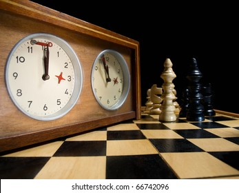 old chess clock on the chessboard with figures ,flag in position which indicates  running out of time