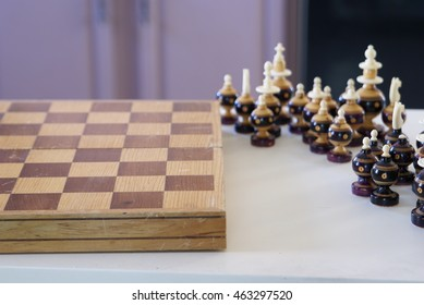 Old chess game board and pieces ready for play.