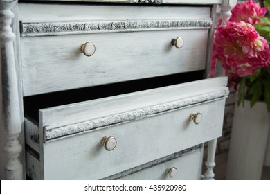 Old chest of drawers with an extended box and flowers