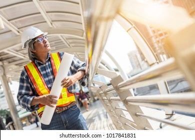 old chief foreman engineer in yellow hard hat holding project plans standing