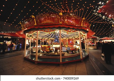 Old children's carousel on Cologne Cathedral Christmas Market at evening.