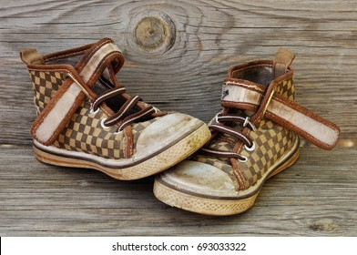 Old children's shoes on the background of the wooden planks.