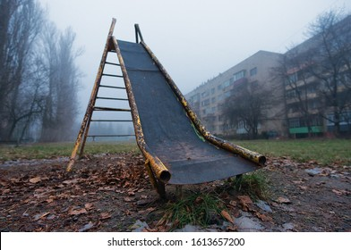 The old children's slide stands on the playground tightened by fog aloone. Yellow paint peeled off. Brown fallen leaves and snow lie before it. Old city buildings in fog on background