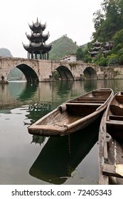 old chinese river boat with bridge and pagoda in the background