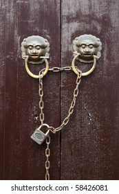 Old Chinese style  door with iron chain and  mythical wild animal head door handles.