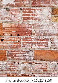 Old, chipped brick wall with broken plaster. Holes in the wall. Weathered surface. Vertical detail.