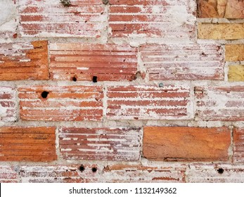 Old, chipped brick wall with broken plaster. Holes in the wall. Weathered surface. Horizontal detail.