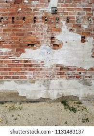 Old, chipped brick wall with concrete foundation & broken plaster. Holes in the wall. White gravel & weeds in the foreground. Vertical view.