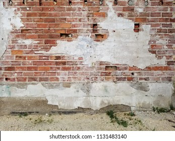 Old, chipped brick wall with concrete foundation & broken plaster. Holes in the wall. White gravel & weeds in the foreground. Horizontal view.