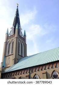 Old Christian church with multiple spires pointing upward into the blue sky, a gold cross atop the tallest one