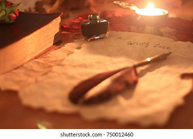 Old Christmas wishlist paper with feather pen and ink, a candle, rose and Bible on wooden table