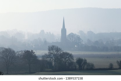 Old church among countryside fields in morning mist. Herefordshire in United Kingdom