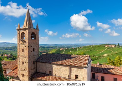 Old church belfry and hills with green vineyards on background under blue sky in Piedmont, Northern Italy.
