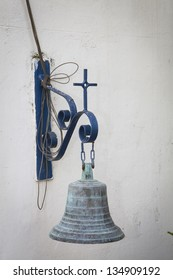 Old church bell on white wall and blue frame
