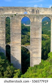 Old church building beyond the pillars of a medieval aqueduct (Ponte delle Torri) in Spoleto, Umbria, Italy