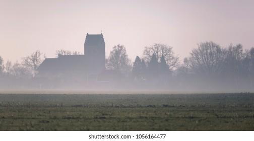 Old church in misty dutch rural landscape. Geesteren, Achterhoek, Gelderland.
