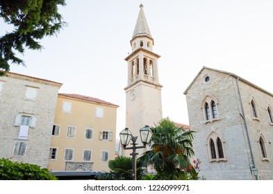 Old Church on the background of palm trees with a tower and bell tower in the old town.