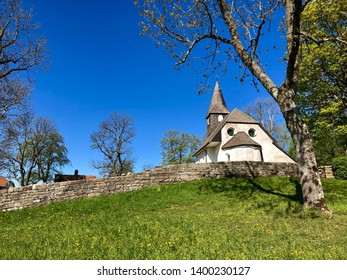 Old church on a hill surrounded by a stone wall a lovely spring day with clear blue sky and greenery.