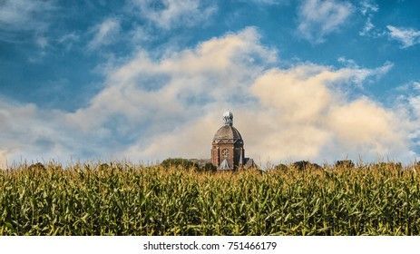 A old church with a red dome in a green cornfield on summer day with  beautiful clouds.