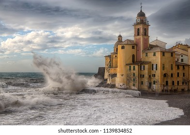 Old church with rough sea and big waves in Camogli, Genoa, (Genova), Italy