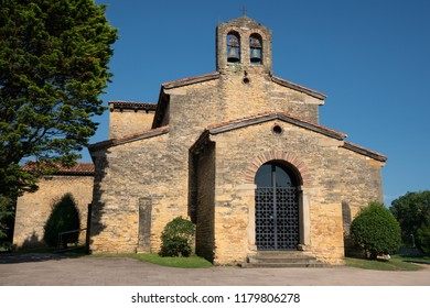 Old Church of San Julian de los Prados with trees and blue sky, Oviedo, Spain