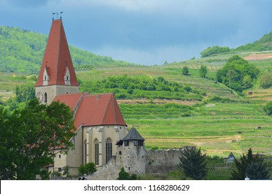 An old church is in a valley, with a vine covered hillside behind it. The church has a red roof and steeple, and high arched windows. An old stone wall with a guard tower is in front of it.