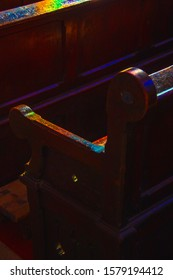 Old church wooden benches colored with sunlight filtered through the stained glass window. Selective focus on pew armrest. God mercy, miracle, hope, religion concepts. Spiritual mystery background.