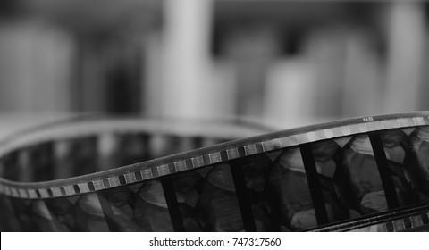 Old cine-film. Film strip on a blur background. Black and white photo.