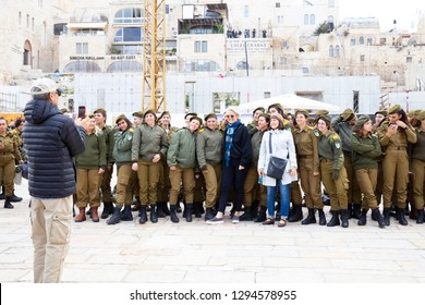 Old City of Jerusalem, Israel - December 24th, 2018: American tourists taking a picture for memory with happy military group girls in the Old city of Jerusalem, Israel.