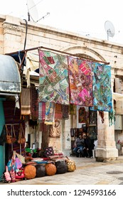 Old City, Jerusalem, Israel - December 24th 2018: A textile shop and vendors having a chat at front of in Christian Quarter, Old City, Jerusalem, Israel.