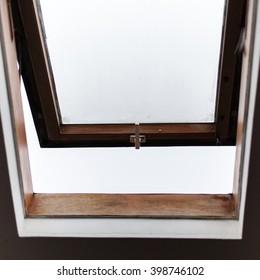 Old city open wooden mansard window in an attic vintage room.
