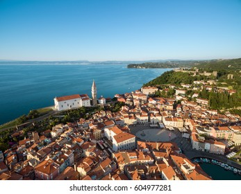 Old city Piran in Slovenia, bird's eye view. Aerial photo with Tartini Square, St. George's Parish Church, old houses, fortress and the sea. Sunset time.