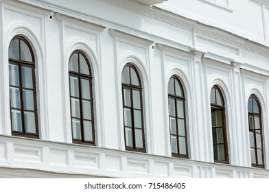 Old city, Prettily suburban town. Architectural details and decoration of the vintage stucco facade framing the windows - console, protome, mascaron, capital, pilasters, wreaths, relief and other.